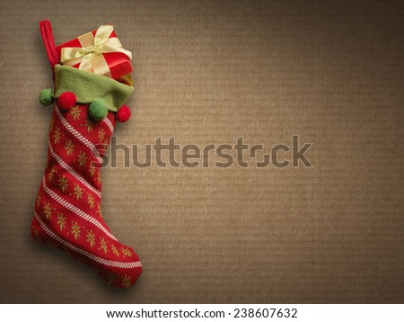 Christmas sock with red gift box on paper background - stock photo