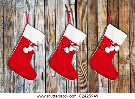Christmas socks hung on a wooden wall - stock photo