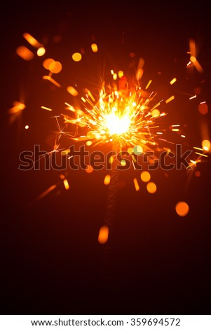 Christmas sparkler in haze with red light - stock photo