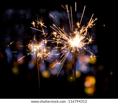christmas sparkler on colorful lights background - stock photo