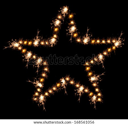 Christmas sparklers in shape of star on black background - stock photo