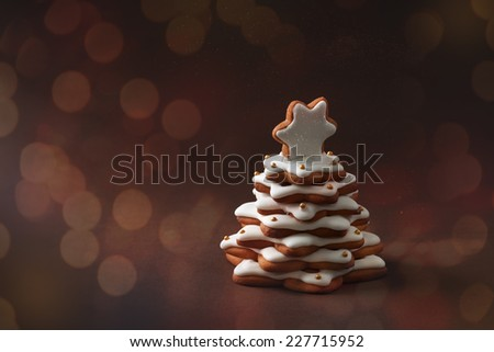 christmas spice cake in the form of fir on the brown background with bokeh - stock photo