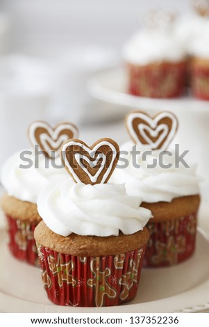 Christmas Spice cupcakes decorated with gingerbread hearts. - stock photo