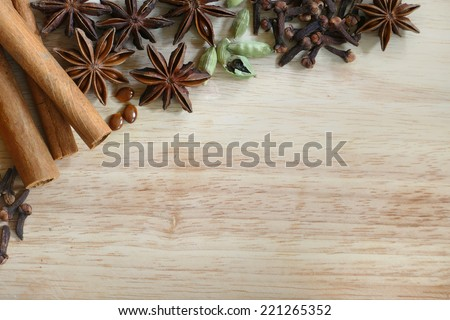 Christmas spices and baking ingredients, cinnamon, cardamom, cloves; anise stars, on a wooden board with copy space - stock photo