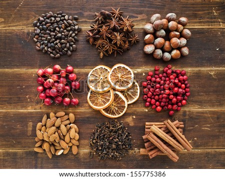 Christmas spices, fruits, nuts and berries on the wooden background. Viewed from above. - stock photo