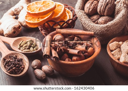 Christmas spices - nuts, brown sugar, dried orange, kandamon, cloves, cinnamon, nutmeg, ginger and anise - stock photo