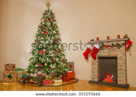 Christmas spirit light and colors in evening living room with decorative mantel, mantelpiece, socks, candles and christmas tree with presents under it. Holidays and home concept - stock photo