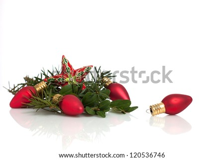 Christmas star and light ornaments with pine and boxwood evergreens.  Isolated on white with reflection. - stock photo