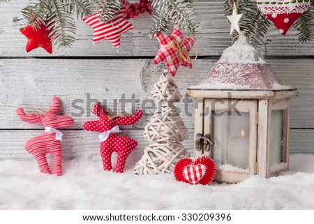 Christmas still life decoration with lantern, cariboo, tree and sledge on wooden background
