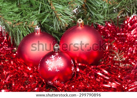 Christmas still life - few red Christmas balls, tinsel on Xmas tree background - stock photo