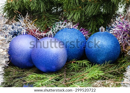 Christmas still life - four blue and violet Christmas baublels, tinsel on Xmas tree background - stock photo