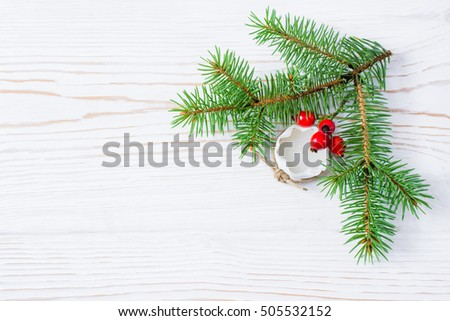 Christmas still-life - fur-tree branches, candle and berries on a wooden background
