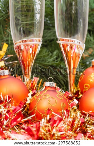 Christmas still life - golden Xmas decorations and two glasses on Christmas tree background - stock photo