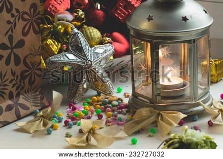 Christmas still life: lantern with burning candle and New Year tree decorations. Aperture 8 - stock photo