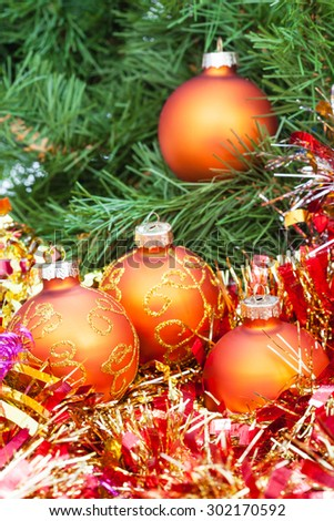 Christmas still life - several orange and yellow Christmas balls, red tinsel on green Xmas tree background - stock photo