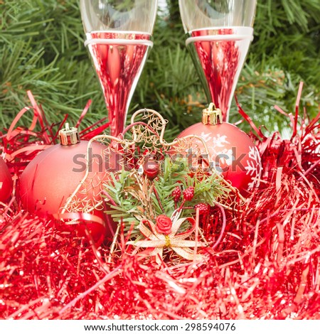 Christmas still life - Two glasses of sparkling wine with red Xmas decorations on Christmas tree background - stock photo