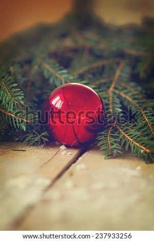 Christmas still life with a  New Year's ball and Christmas tree branch on old table - stock photo