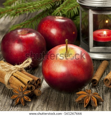 Christmas still life with apple and lantern on a wooden surface