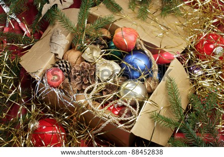 Christmas still-life with baubles, twigs, nuts, tinsel, candles in a box. - stock photo