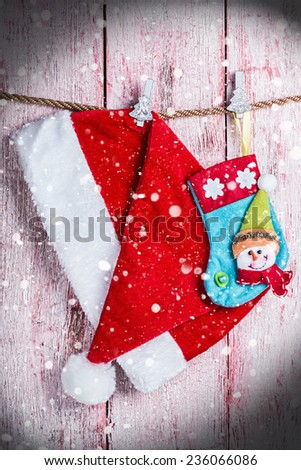 Christmas stocking and Santa hat on a background of falling snow - stock photo