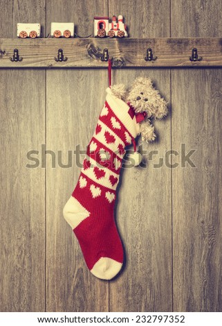 Christmas stocking filled with teddy bear and train set on ledge - stock photo