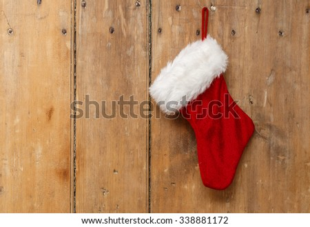 Christmas stocking hanging on an old pine wooden door - stock photo