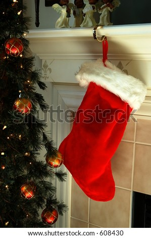 Christmas Stocking hanging on the Fireplace Mantle next to  the Christmas tree in preparation for Santa's arrival on Christmas Eve. - stock photo
