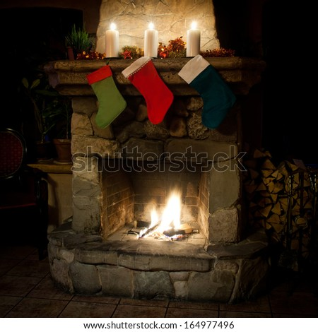 Christmas stocking on fireplace background. Chimney, candles and woodpile. (vintage chiar). (front view) - stock photo