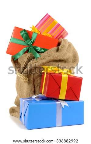 Christmas stocking or sack full with pile of Christmas gifts isolated on white background - stock photo