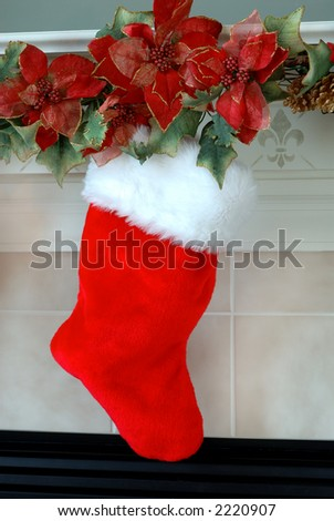 Christmas Stocking - Red and white fur christmas stocking hangs on the mantle above the fireplace on Christmas Eve. - stock photo