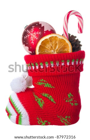 Christmas stocking stuffed with ball, orange and a candy, isolated on a white background - stock photo