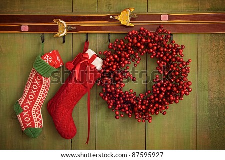 Christmas stockings and wreath hanging on rustic wall - stock photo