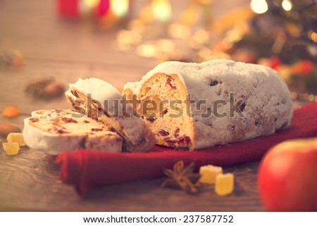 Christmas Stollen. Traditional Sweet Fruit Loaf with Icing Sugar. Xmas holiday table setting, decorated with garlands, baubles, wallnuts, hazelnuts, cinnamon sticks. Warm colors toned. Vintage styled - stock photo
