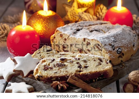 Christmas stollen with candles cinnamon stars cinnamon sticks pine twig nuts on wooden board - stock photo