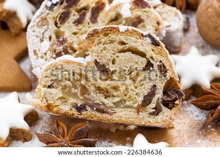 Christmas Stollen with dried fruit, assorted cookies and spices, close-up, horizontal - stock photo