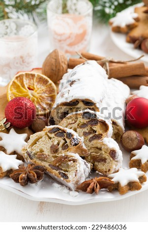 Christmas Stollen with dried fruit, cookies and spices on a plate, vertical - stock photo
