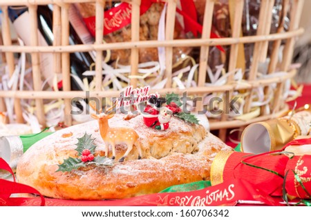 Christmas stollen with reindeer and santa claus topper with a hamper basket at the background - stock photo