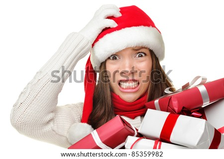 Christmas stress - busy woman wearing santa hat stressing for christmas shopping holding may christmas gifts in her arms. Funny image of Asian Caucasian female model isolated on white background. - stock photo