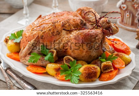 Christmas Stuffed  Chicken Served with Potatoes, Carrots and Figs on a Wooden Table - stock photo
