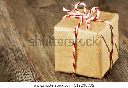 Christmas style rustic brown paper package tied up with strings - stock photo