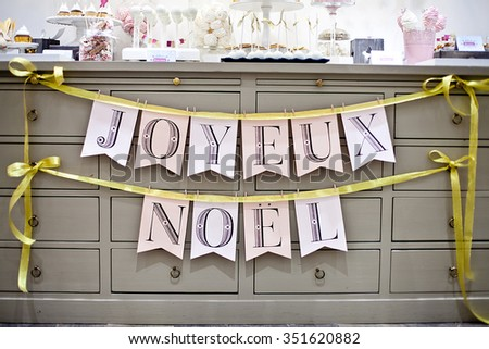 "Christmas sweet table or candy bar. Holiday decoration. Paper garland with french sign  ""Happy holidays""."