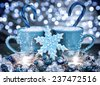 Christmas sweets still life, two blue coffee cups with candy inside and snowflake shape gingerbread on the home table, traditional Christmastime dessert - stock photo
