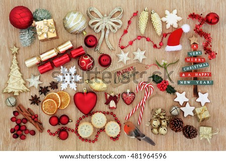 Christmas symbols with tree decorations, baubles, mince pies, gingerbread biscuits,spices, fruit and gift tag over oak wood background.