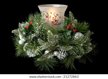 Christmas table centerpiece with hurricane glass, glowing candle and frosted greenery, isolated on black - stock photo