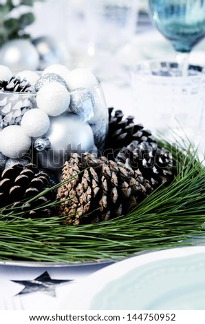 Christmas table decoration with pine cones, pine needles and crockery place setting - stock photo