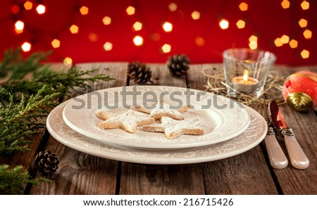 Christmas table - elegant white plate with cookies, natural pine tree branch and pinecones on vintage planked wood. Rural or rustic style table setting on red backdrop with blurred lights. - stock photo