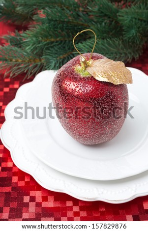 Christmas table place setting with a decorative apple on red napkin - stock photo