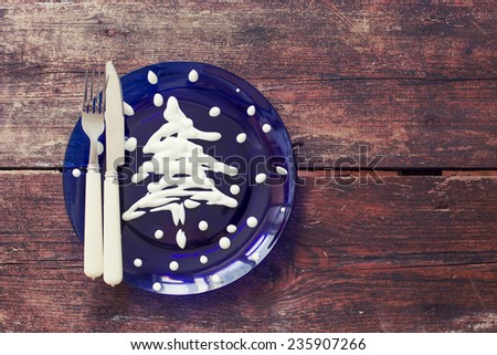 Christmas table place setting with christmas tree on the plate on wooden background - stock photo