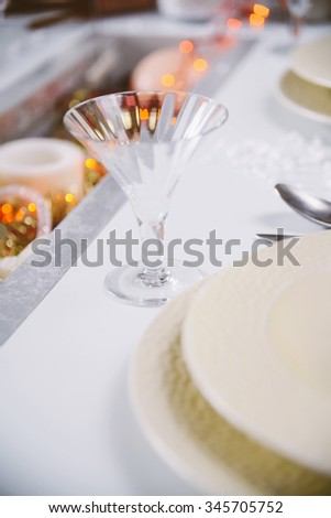 Christmas table setting - elegant white plate on decorative table with candles and shiny ornaments on the middle.Rustic or vintage style.Dining table setting/Christmas decorative set table - stock photo