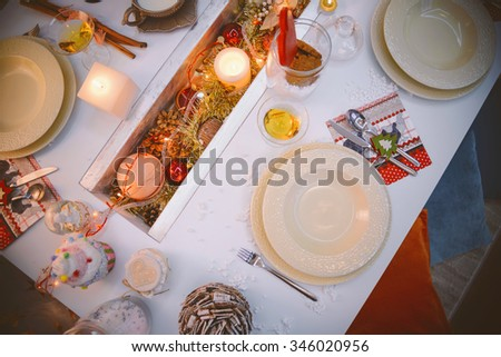 Christmas table setting from above - elegant white plate on decorative table with candles and shiny ornaments on the middle.Rustic or vintage style.Dining table setting/Christmas decorative set table - stock photo